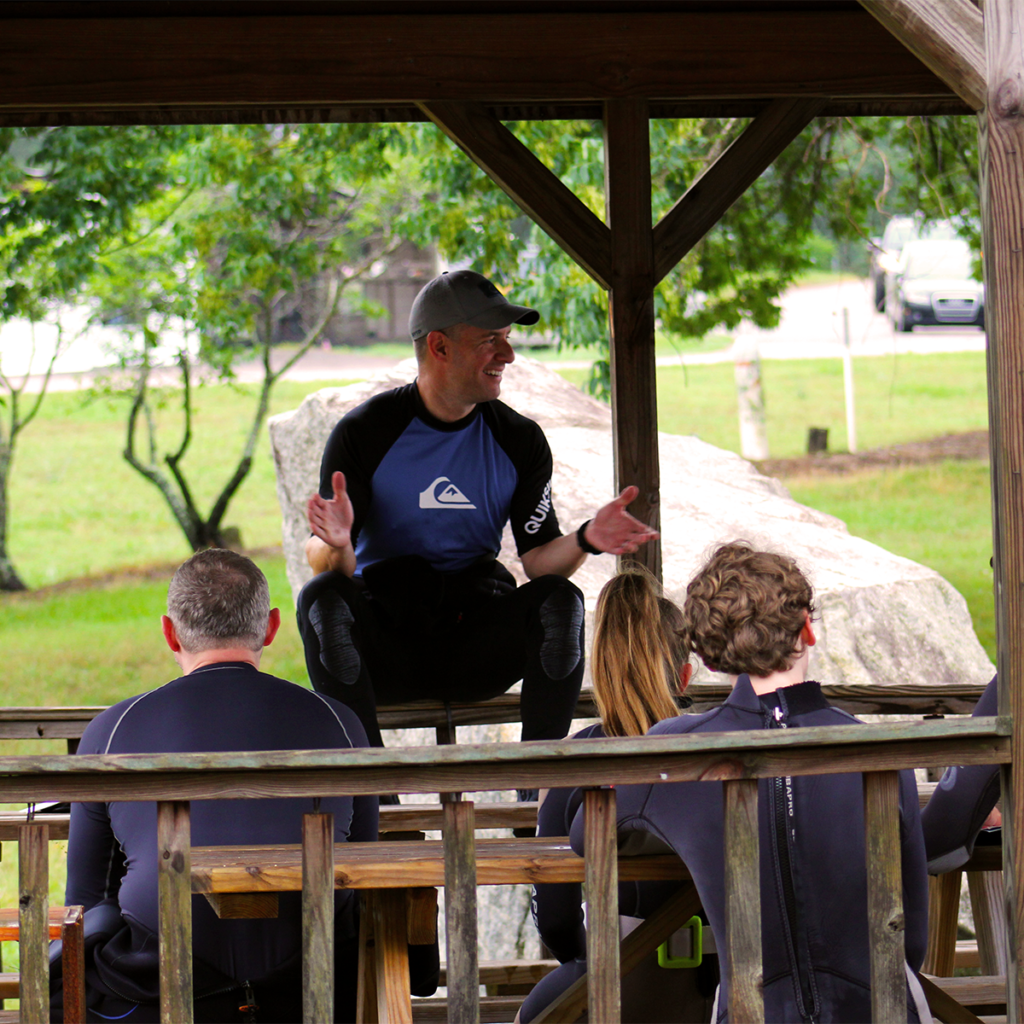 A dive instructor going over a dive brief with his students