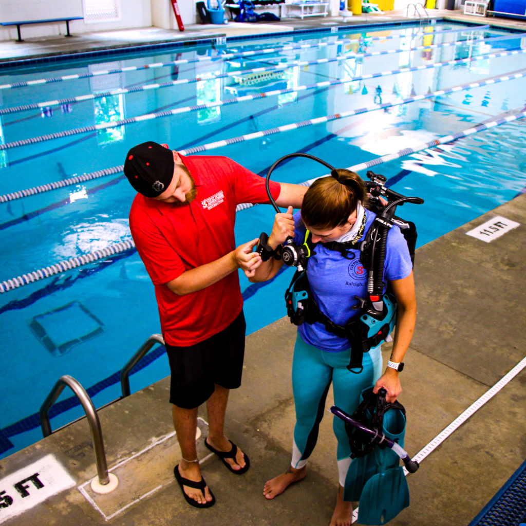 A dive instructor reminding a student to check their computer