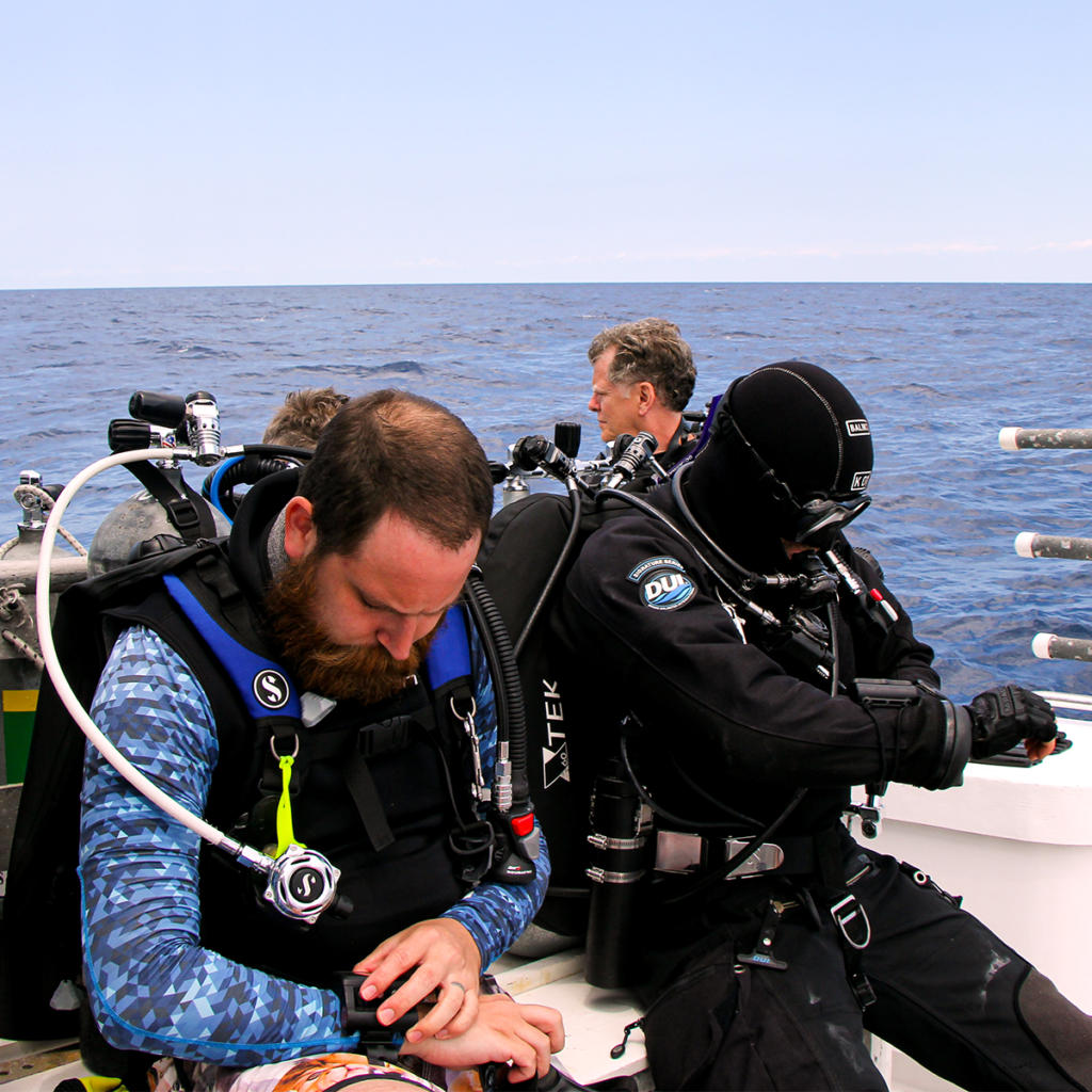 Two divers checking their computers before a dive