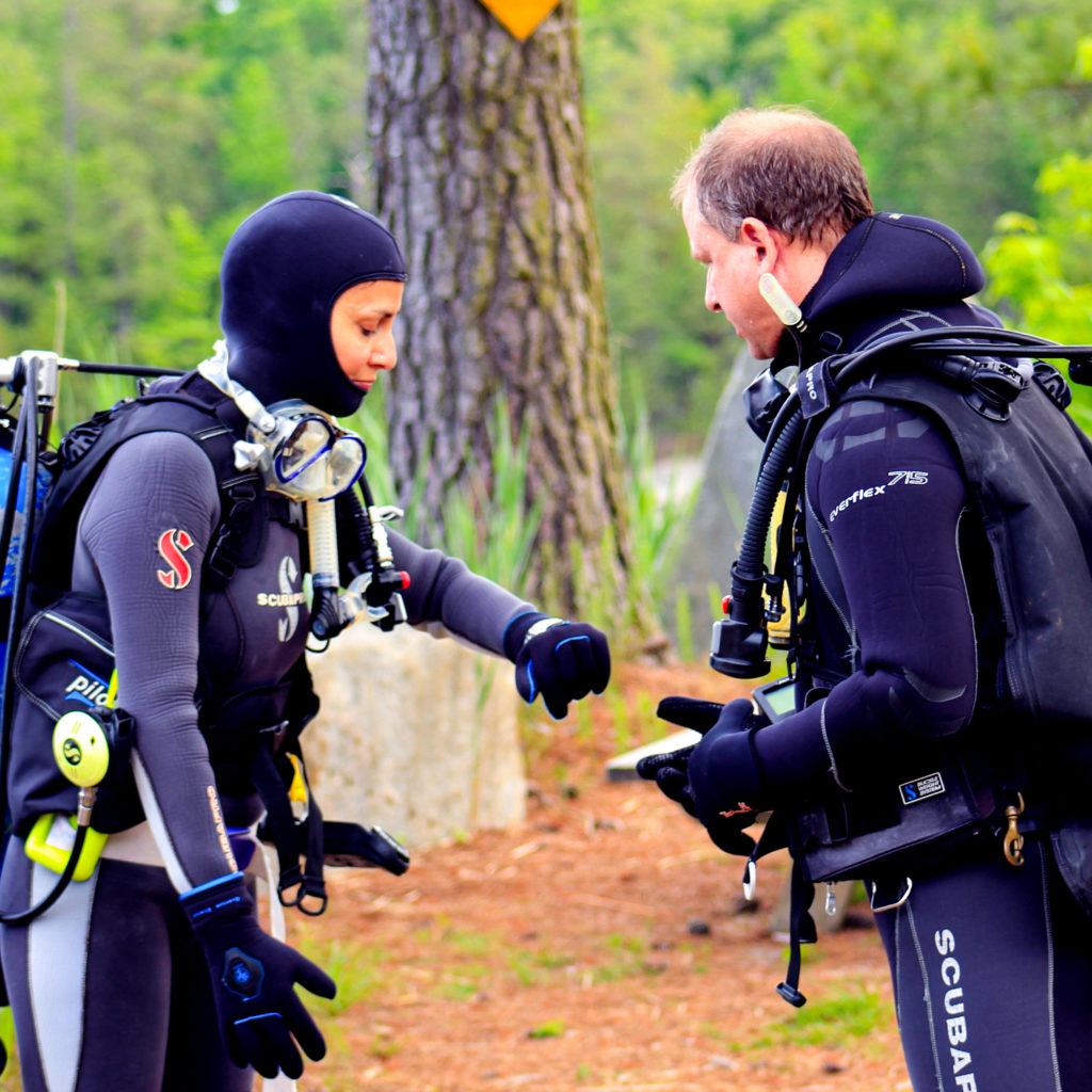 A dive instructor going over last checks before a checkout dive