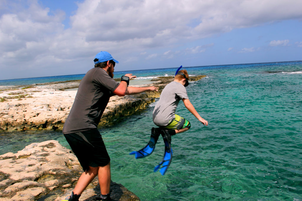 A dive instructor helping a young diver get a large jump into the ocean