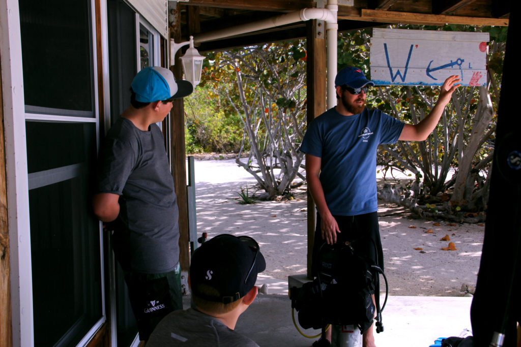 A Gypsy instructor going over equipment safety before a dive in Cayman Brac