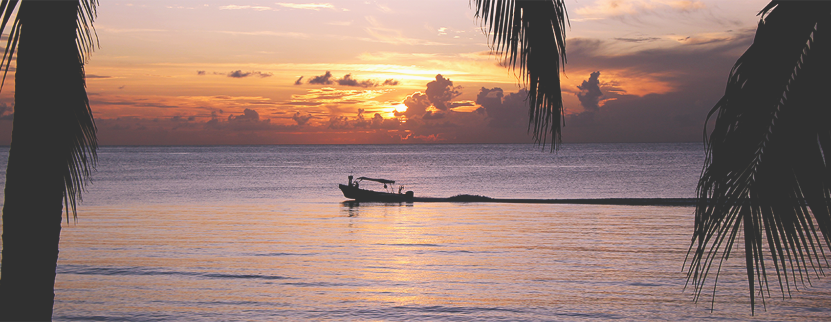 A boat driving by during a sunset in Cozumel