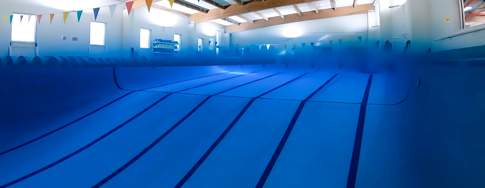 A split image of our Gypsy Divers' training pool, half underwater and half above