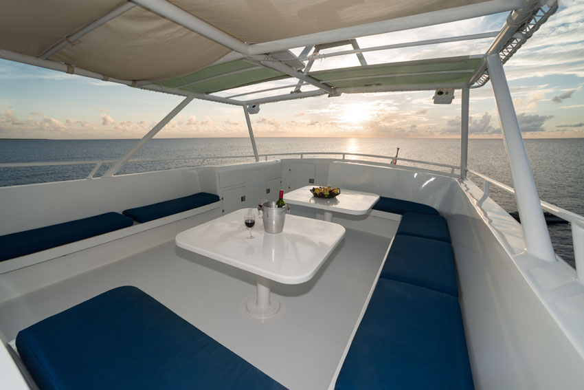The fly bridge on the Turks and Caicos Explorer II. A sunset is seen in the background over the blue seats and tables.