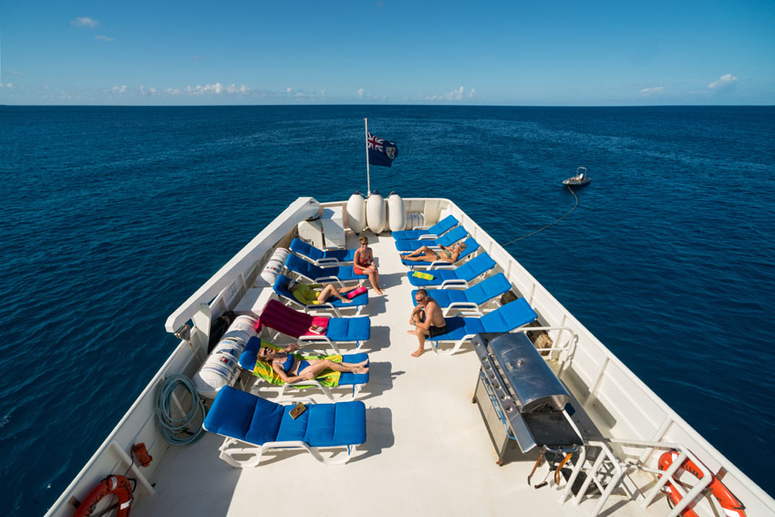 The sun deck on the Turks and Caicos Explorer II. Several chairs are spread out with people laying in the sun.