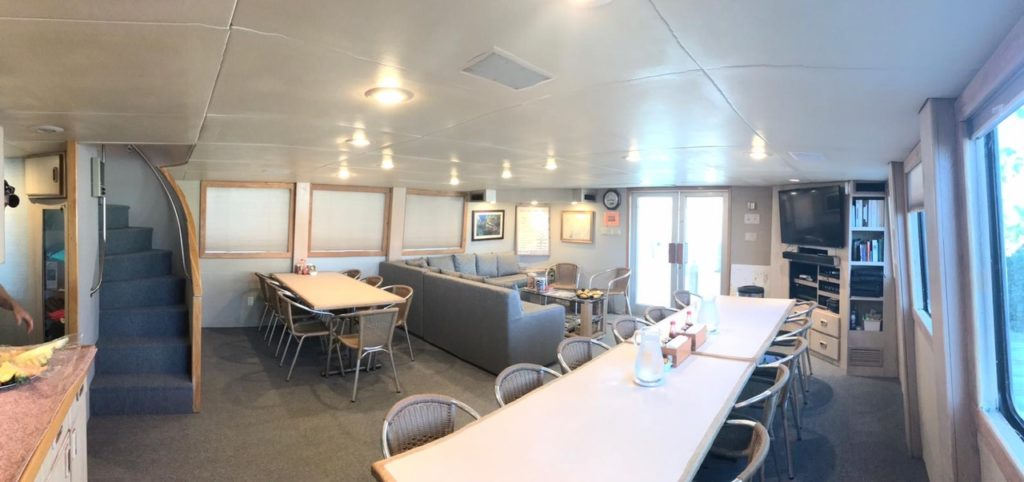 The dining and lounge area of the Turks and Caicos Explorer II. Several tables with seats around for eating dinner and sofas for lounging