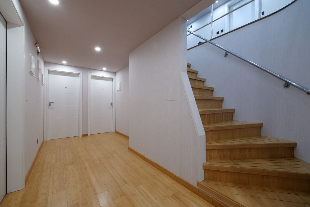 Hallway in the Emperor Explorer, sleek white whiles and light wood stairs lead down to two bedroom doors.