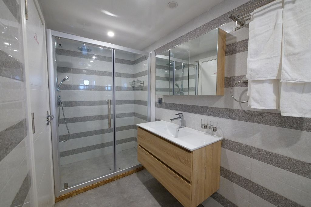 The lower deck bathrooms of the Emperor Explorer show a glass sliding door leading into a spacious shower and nice wooden finished sink. The whole room is tiled in bright white and grey tiles.