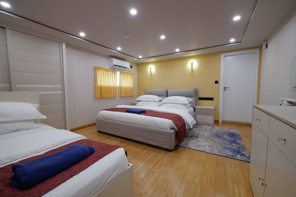 The Main Deck Suite of the Emperor Explorer shows an expansive room with two beds. The beds are surrounded by white walls and furniture with wooden floors.