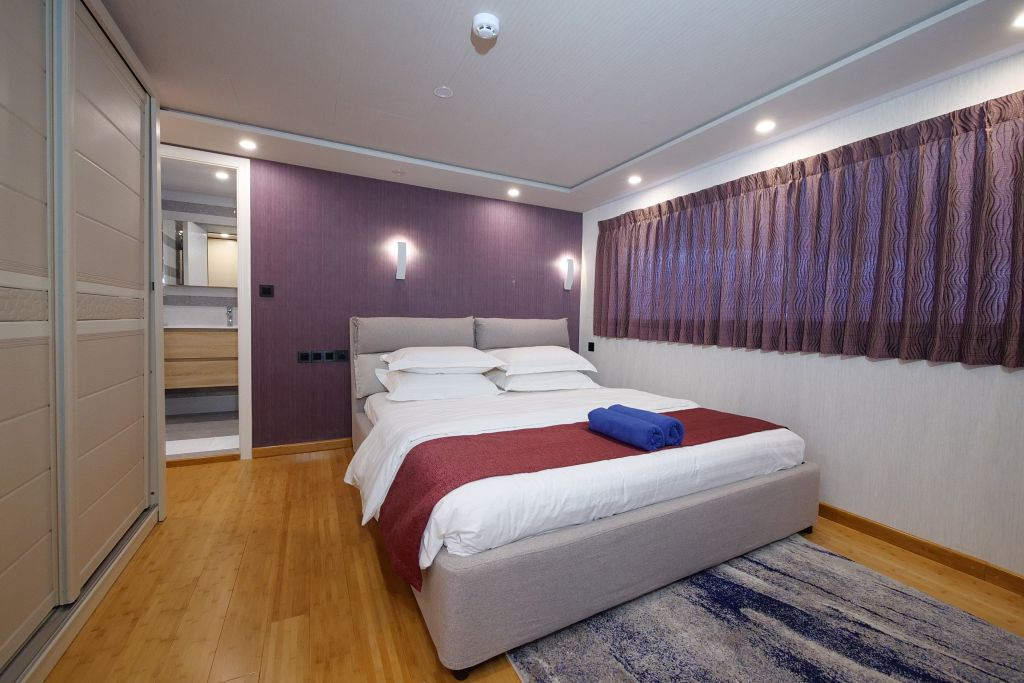 The upper deck suite of the Emperor Explorer shows a large bed with white sheets and red accent blanket. The walls are deep purple and white with light wood floors.